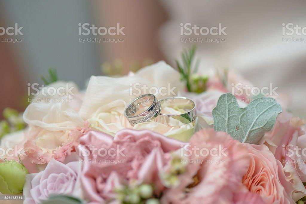 Primer tiro de pastel ramo de rosas y seda con dos anillos de boda en una rosa blanca, lista para la ceremonia de la boda - foto de stock