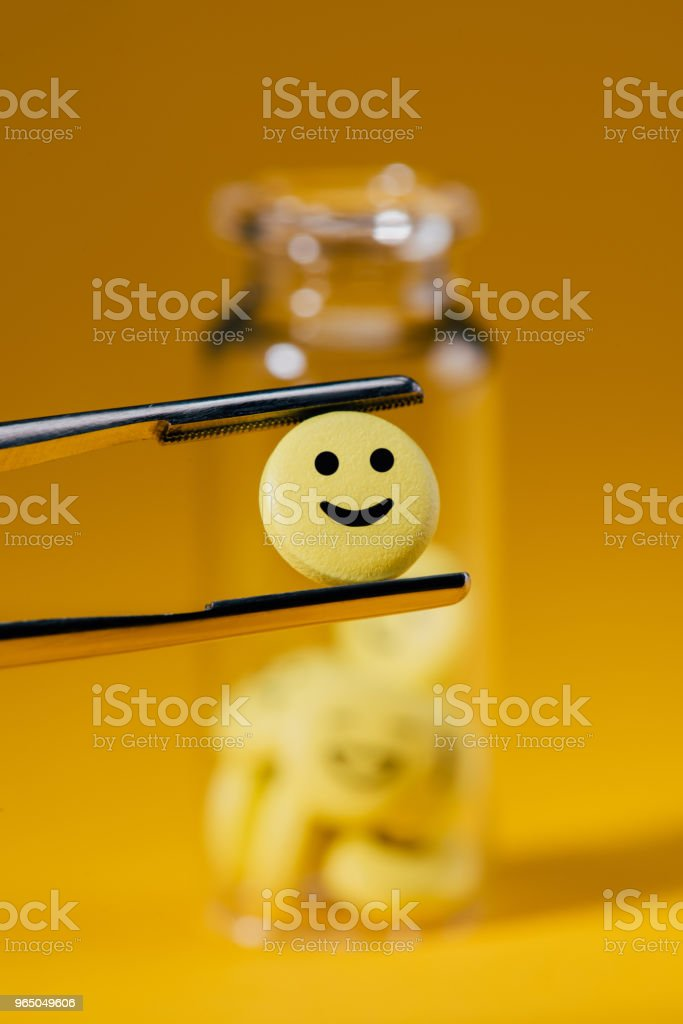 close-up shot of pill with smiley face in tweezers and glass bottle on yellow royalty-free stock photo