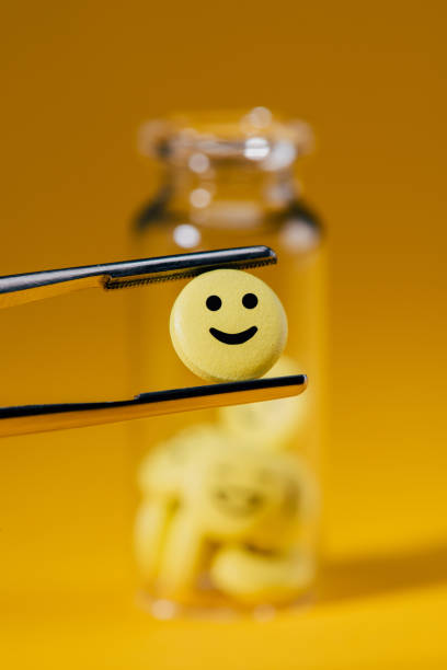 close-up shot of pill with smiley face in tweezers and glass bottle on yellow - excited emoji stock photos and pictures