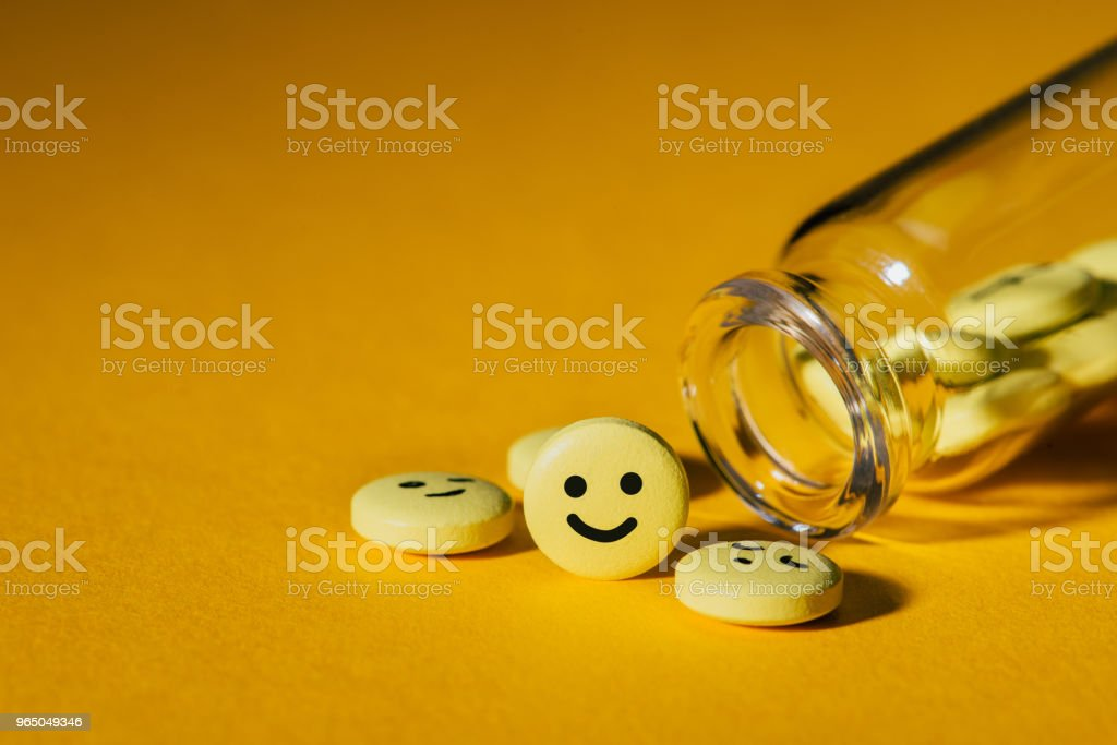 close-up shot of pills with smiley faces and glass bottle on yellow royalty-free stock photo