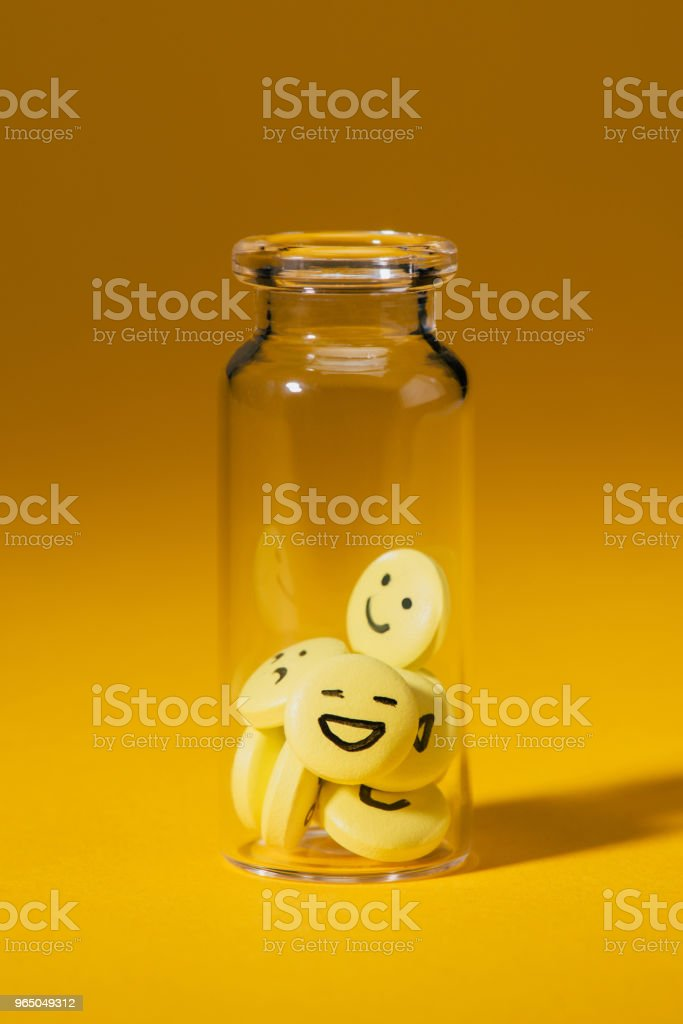 close-up shot of pills with smiley faces in glass bottle on yellow zbiór zdjęć royalty-free