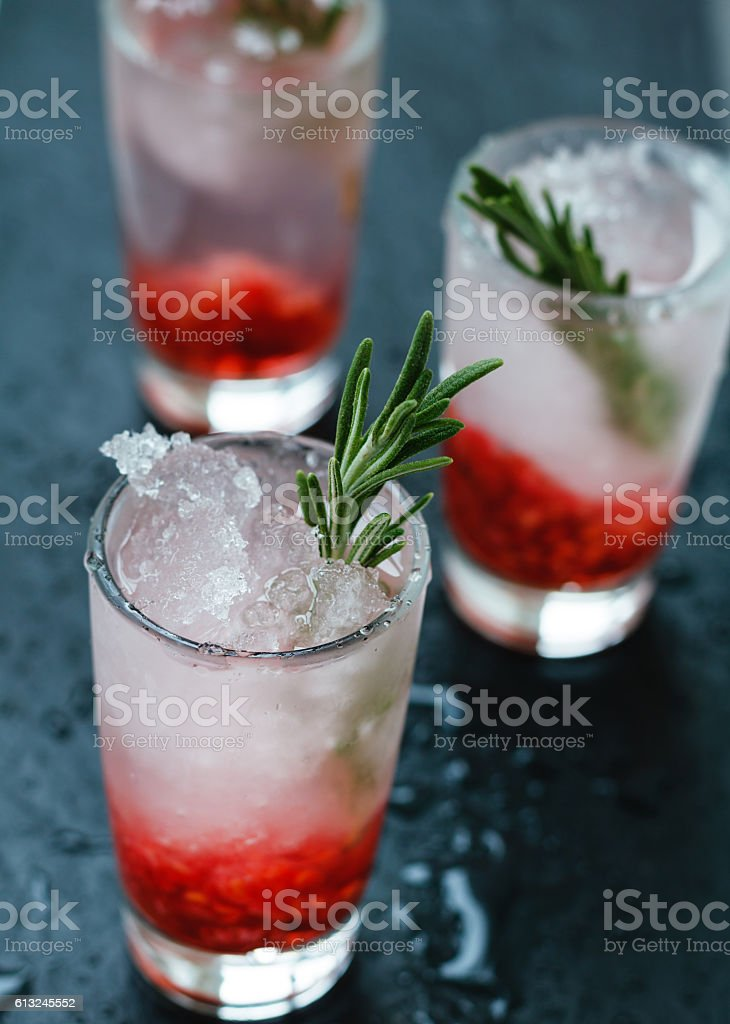 Close-up shot of refreshing berry cocktails with ice and rosemary stock photo