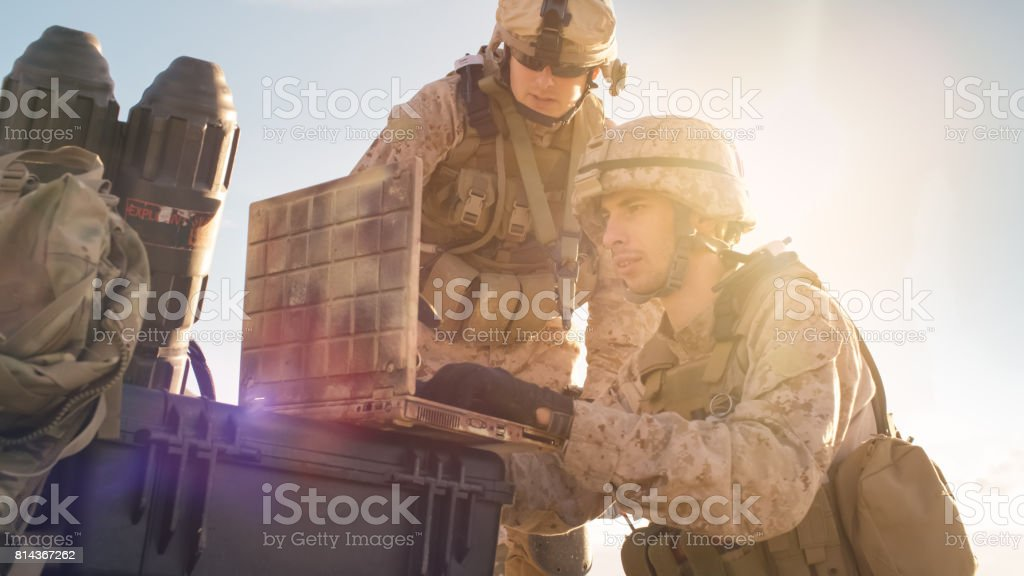 Close-up shot of Soldier is Using Laptop Computer for Surveillance During Military Operation in the Desert. stock photo