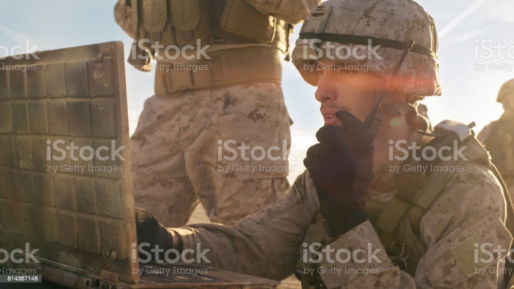 Close-up shot of Soldier Using Radio For Communication During Military Operation in the Desert. stock photo