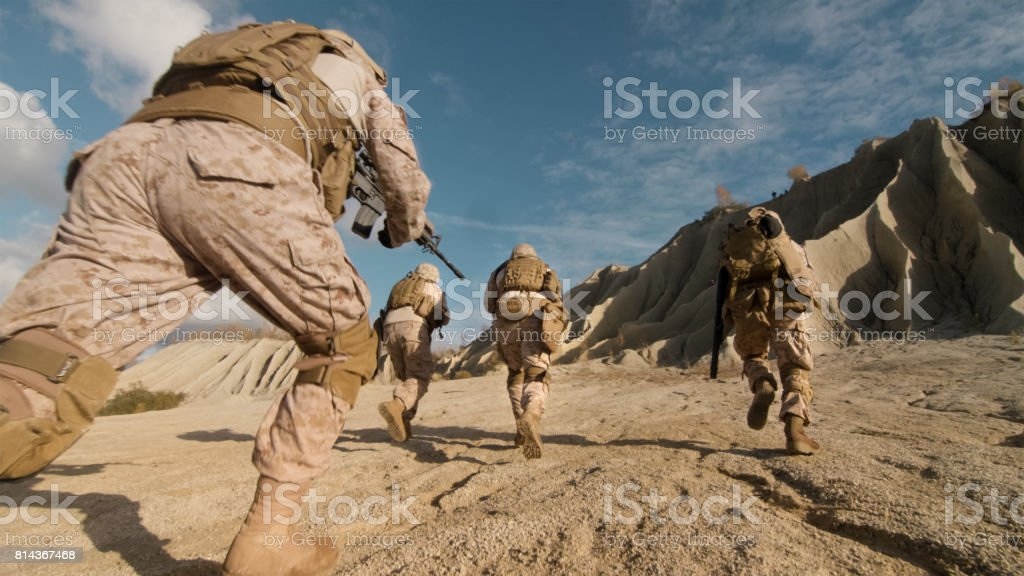 Close-up Shot of Squad of Soldiers Running Forward and Atacking Enemy During Military Operation in the Desert. stock photo