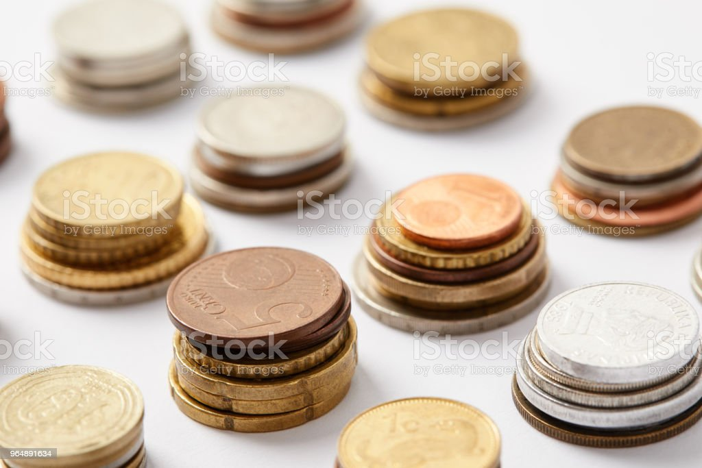 close-up shot of stacks of coins from various countries on white royalty-free stock photo