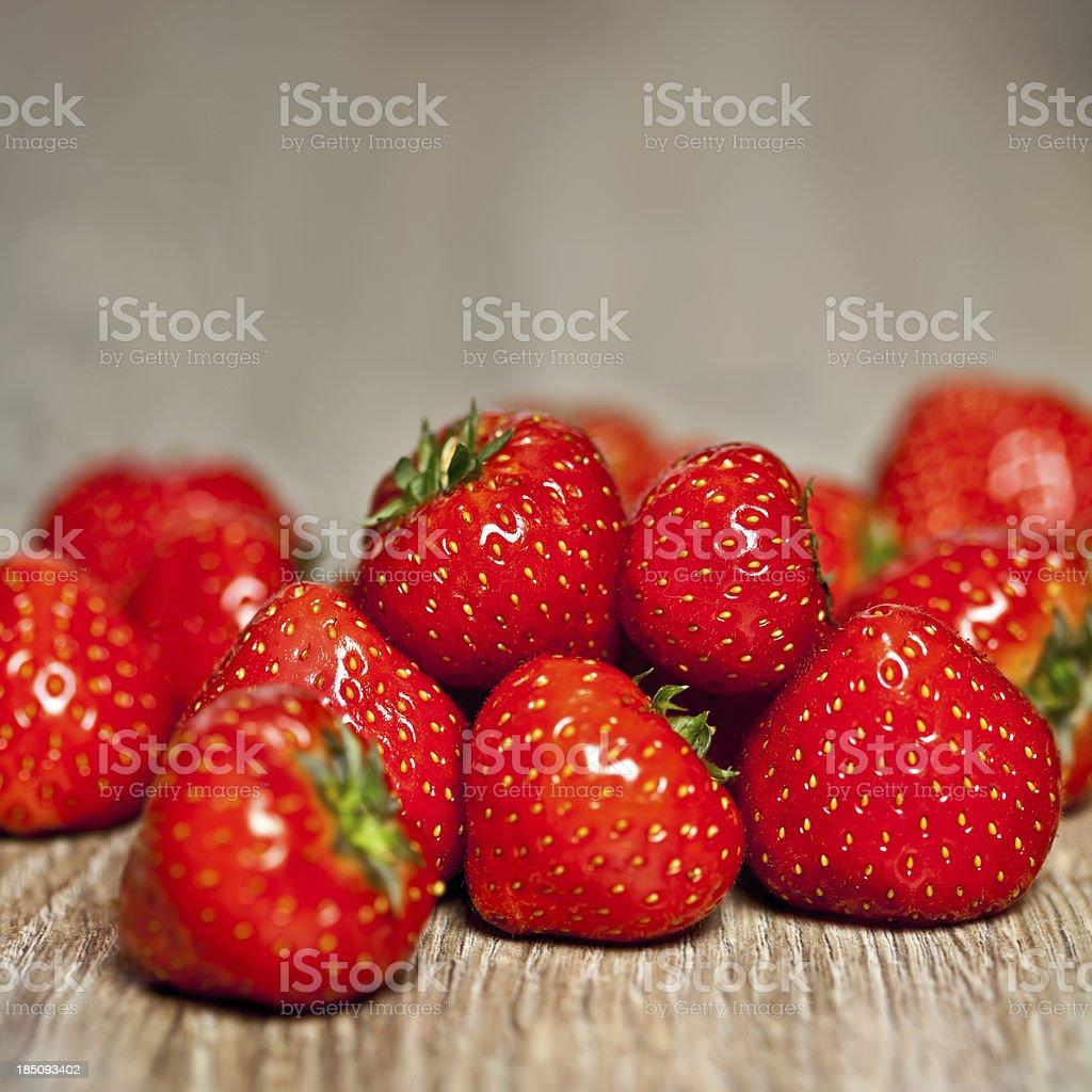 Close-up shot of strawberry on hardwood floor royalty-free stock photo