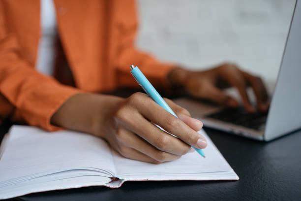 zbliżenie ręki studenta trzymającego długopis i piszącego w notatniku, pracującego w domu. e-learning - notes zdjęcia i obrazy z banku zdjęć