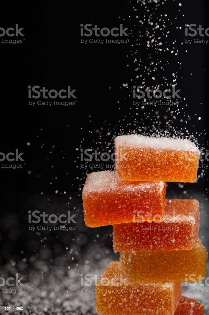 closeup shot of sugar falling on jelly candies on black background royalty-free stock photo