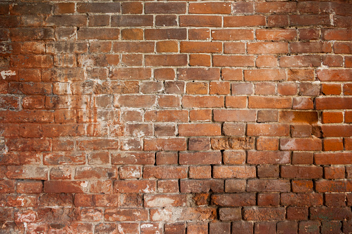 A close-up shot of the old rough brick masonry wall lined with red clumsy brick for creativity, textures and background.
