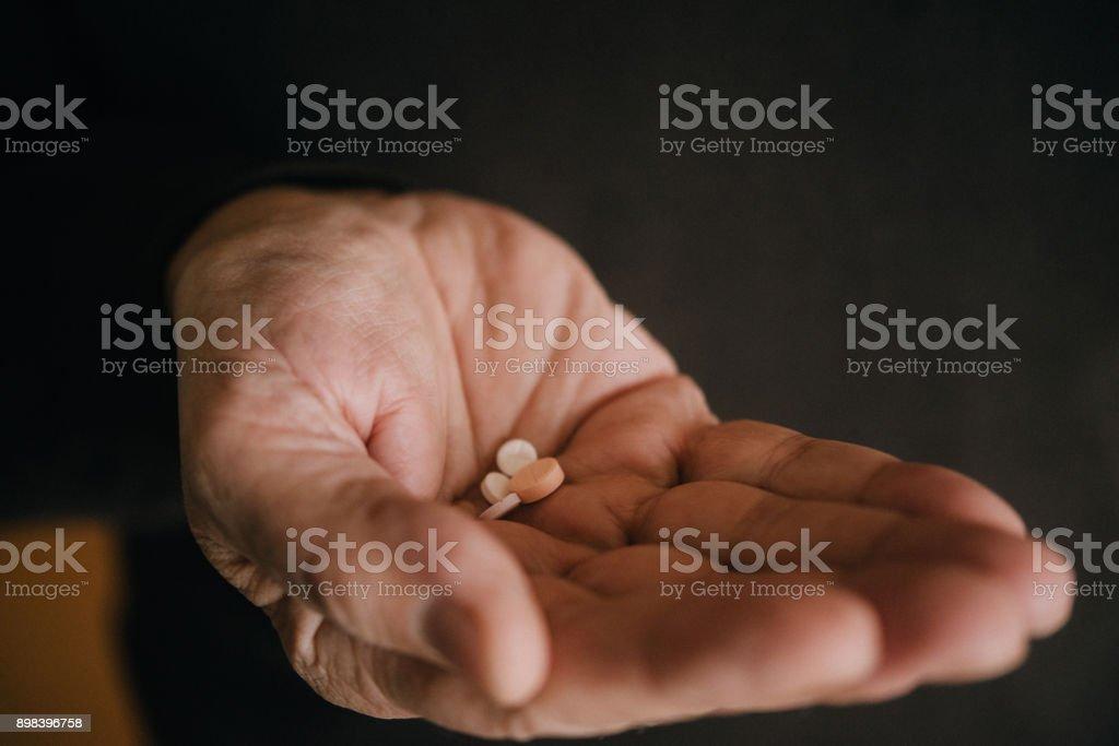 Close-up shot of the senior man holding pills stock photo