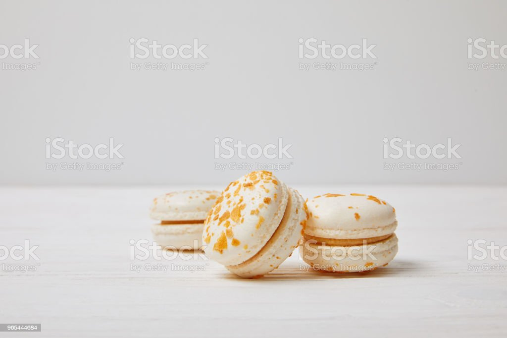 closeup shot of three macarons on white wooden table royalty-free stock photo