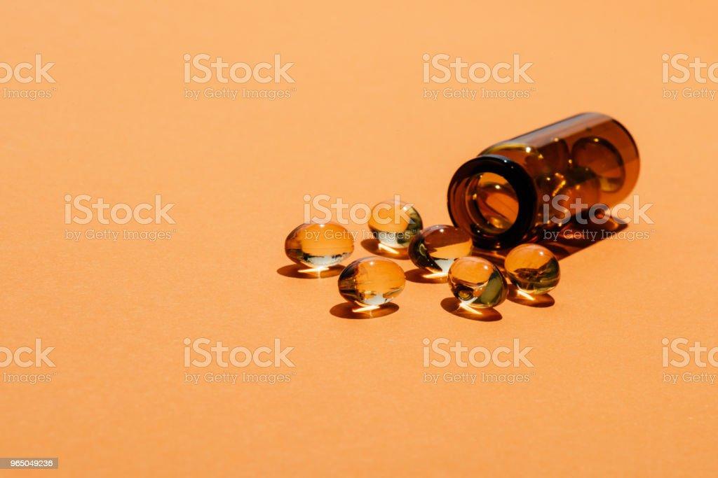 close-up shot of transparent yellow pills spilled from bottle on orange surface zbiór zdjęć royalty-free