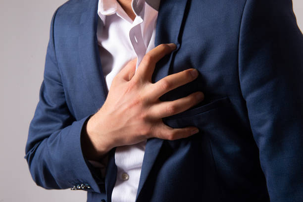 Close-up shot of unrecognizable businessman having chest pain - heart attack - midsection of young man holding his heart in pain against gray background