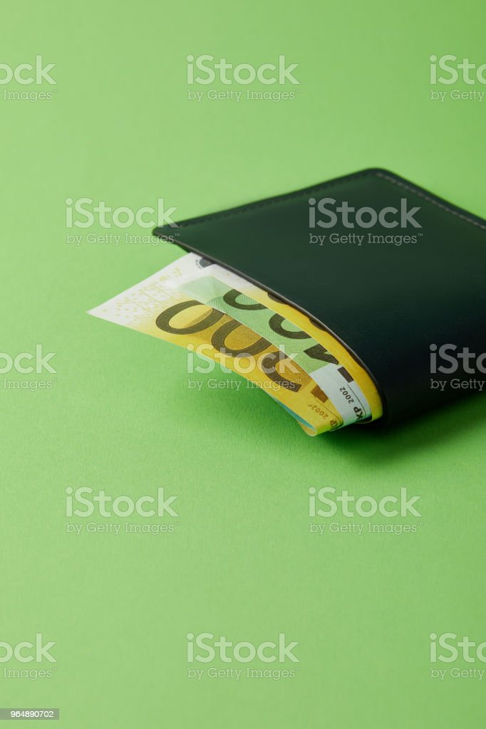 close-up shot of wallet with euro banknotes on green surface royalty-free stock photo