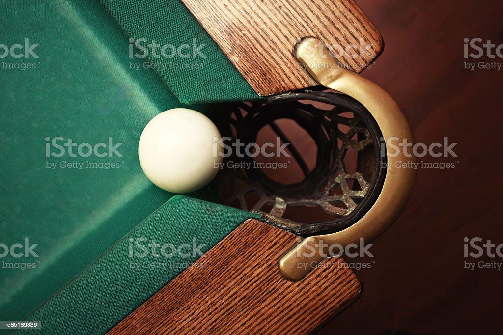 Closeup shot of white ball going in billiard pocket stock photo