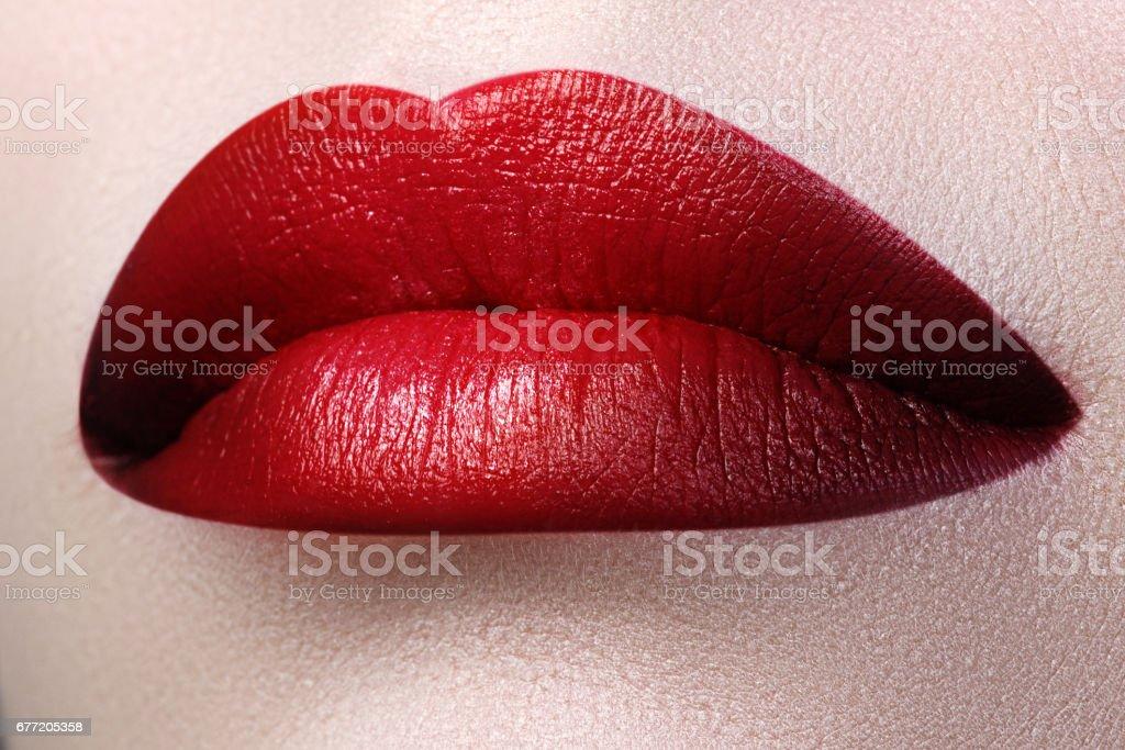 Close-up shot of woman lips with red lipstick. Beautiful perfect stock photo