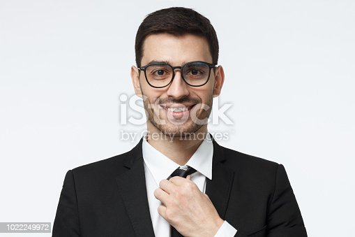 istock Closeup shot of young business man in spectacles pictured isolated on grey background, straightening his tie, looking positive and confident, satisfied with success of his team 1022249972
