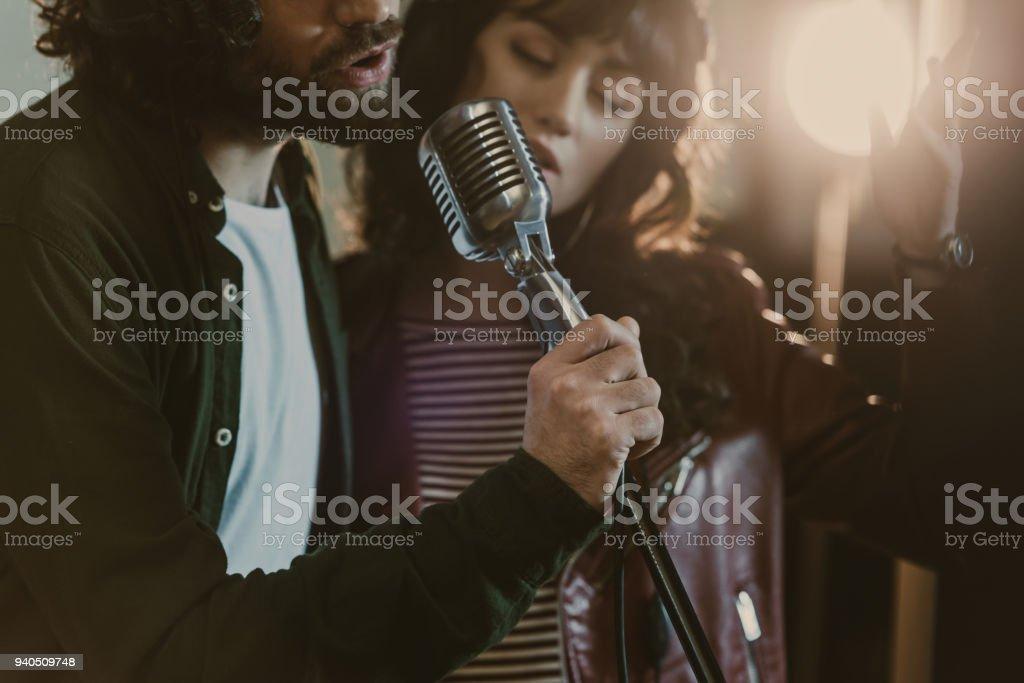 Nahaufnahme des jungen Paares Durchführung Song mit Vintage Mikrofon erschossen – Foto