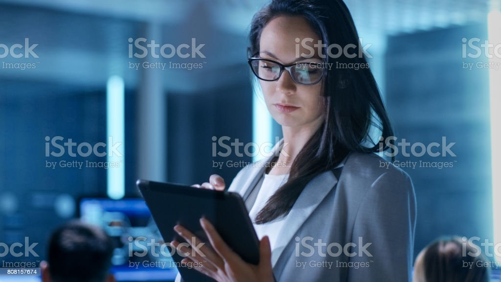 Close-up Shot of Young Female Government Employee Wearing Glasses Uses Tablet in System Control Center. In the Background Her Coworkers are at Their Workspaces with many Displays Showing Valuable Data. stock photo