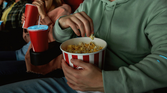 Closeup shot of young guy having popcorn basket while watching movie in cinema auditorium together with friends. Entertainment and people concept. Web Banner