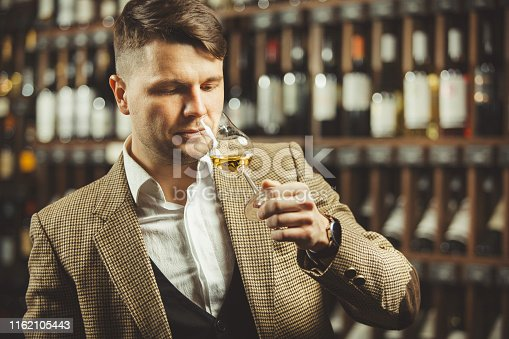 Close-up shot of young sommelier smell whiskey on cellar background. Expert in the field of alcoholic beverages.