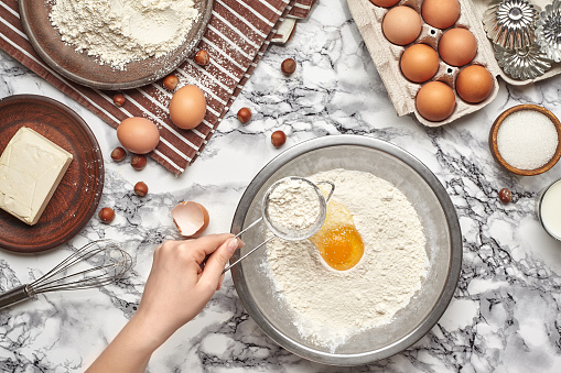 istock Close-up shot. Top view of a baker cook place, hands are working with a raw dough on the marble table background. 1153389324