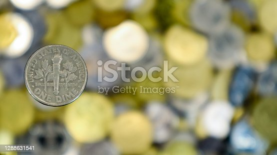A close-up shows one 10 cent or 0.1 US dollar coin. This is money. Blurred money background. The 10 cent dime is the smallest of all coins. The reverse depicts a torch, oak and olive branches