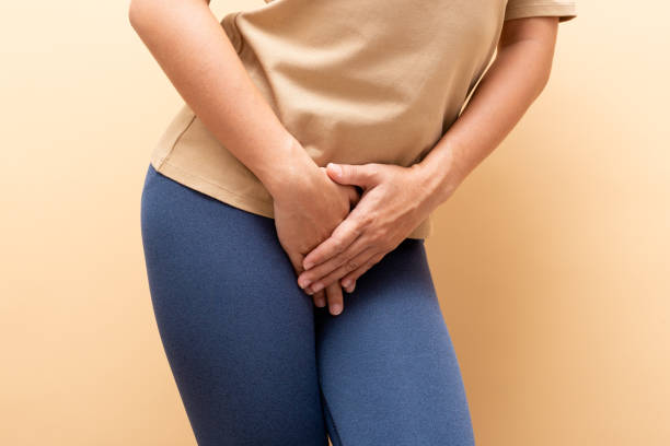 Closeup sick woman with hands holding pressing her crotch isolated on background stock photo