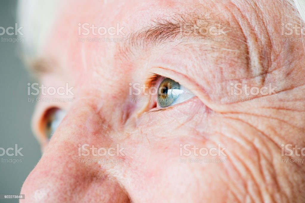 Closeup side portrait of white elderly woman's eyes stock photo