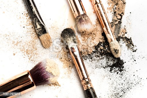 istock Close-up side view of professional make-up brush with natural bristle and black ferrule with crashed eyeshadow isolated on white background 1081292912