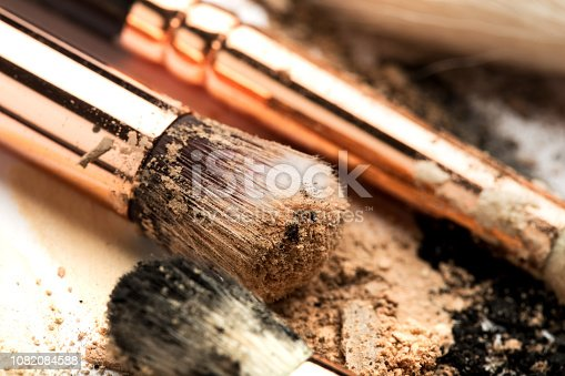 861986852 istock photo Close-up side view of professional make-up brush with natural bristle and black ferrule with crashed eyeshadow isolated on white background 1082084588