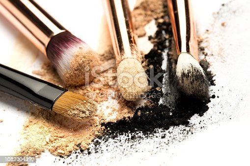 861986852 istock photo Close-up side view of professional make-up brush with natural bristle and black ferrule with crashed eyeshadow isolated on white background 1082304392