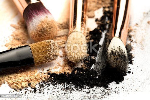 istock Close-up side view of professional make-up brush with natural bristle and black ferrule with crashed eyeshadow isolated on white background 1082421476
