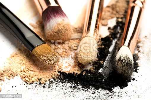 istock Close-up side view of professional make-up brush with natural bristle and black ferrule with crashed eyeshadow isolated on white background 1083574724