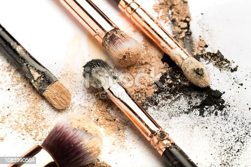 istock Close-up side view of professional make-up brush with natural bristle and black ferrule with crashed eyeshadow isolated on white background 1083990504