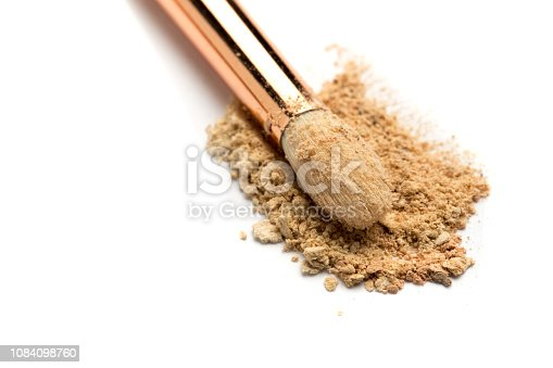 861986852 istock photo Close-up side view of professional make-up brush with natural bristle and black ferrule with crashed eyeshadow isolated on white background 1084098760