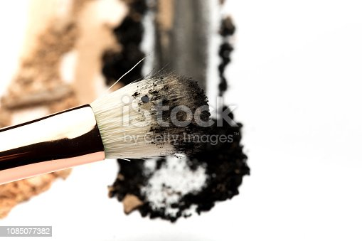 861986852 istock photo Close-up side view of professional make-up brush with natural bristle and black ferrule with crashed eyeshadow isolated on white background 1085077382