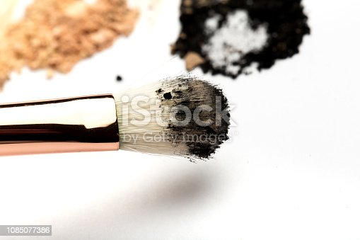 861986852 istock photo Close-up side view of professional make-up brush with natural bristle and black ferrule with crashed eyeshadow isolated on white background 1085077386