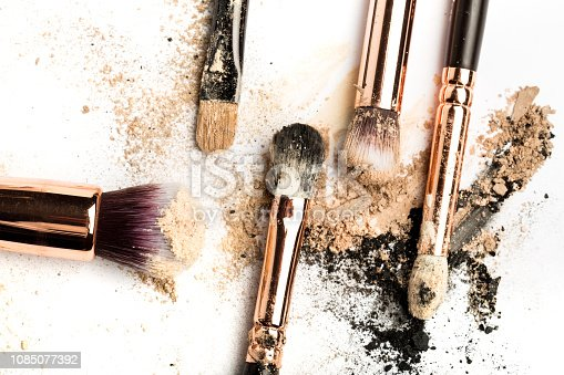 861986852 istock photo Close-up side view of professional make-up brush with natural bristle and black ferrule with crashed eyeshadow isolated on white background 1085077392