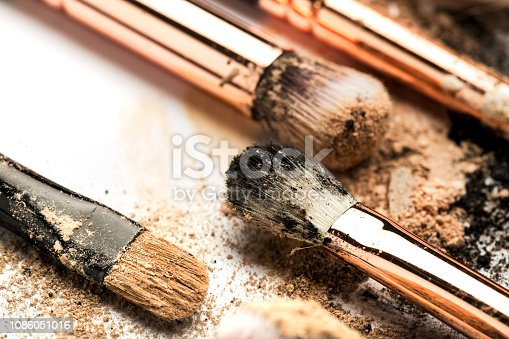 istock Close-up side view of professional make-up brush with natural bristle and black ferrule with crashed eyeshadow isolated on white background 1086051016