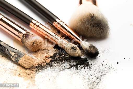 861986852 istock photo Close-up side view of professional make-up brush with natural bristle and black ferrule with crashed eyeshadow isolated on white background 1125834812