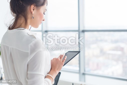 istock Close-up side view portrait of an employee texting, sending and reading messages during her break at the workplace. 695140720