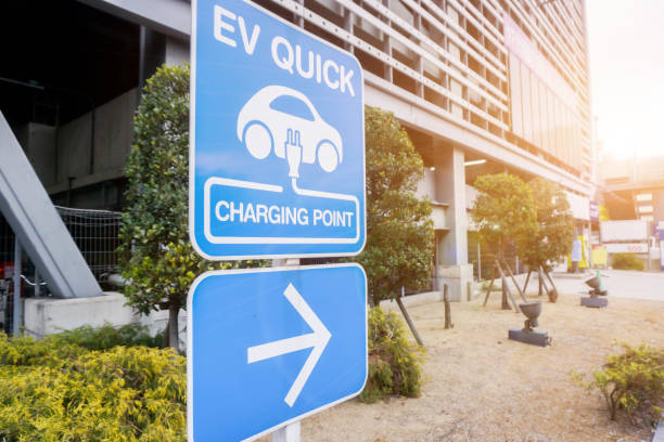 closeup sign and symbol of Electric car charging point with navigation arrow on blurry building and sun flare Perspective view and closeup sign and symbol of Electric car charging point with navigation arrow on blurry building and sun flare background. electric vehicle charging station stock pictures, royalty-free photos & images