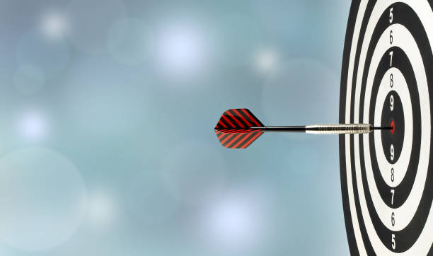closeup silver metal dart arrow hitting red bulls eye target center of wooden dartboard with blurred blue lights bokeh copy space background perfection goal success, symbol of aim and achievement bull's eye stock pictures, royalty-free photos & images