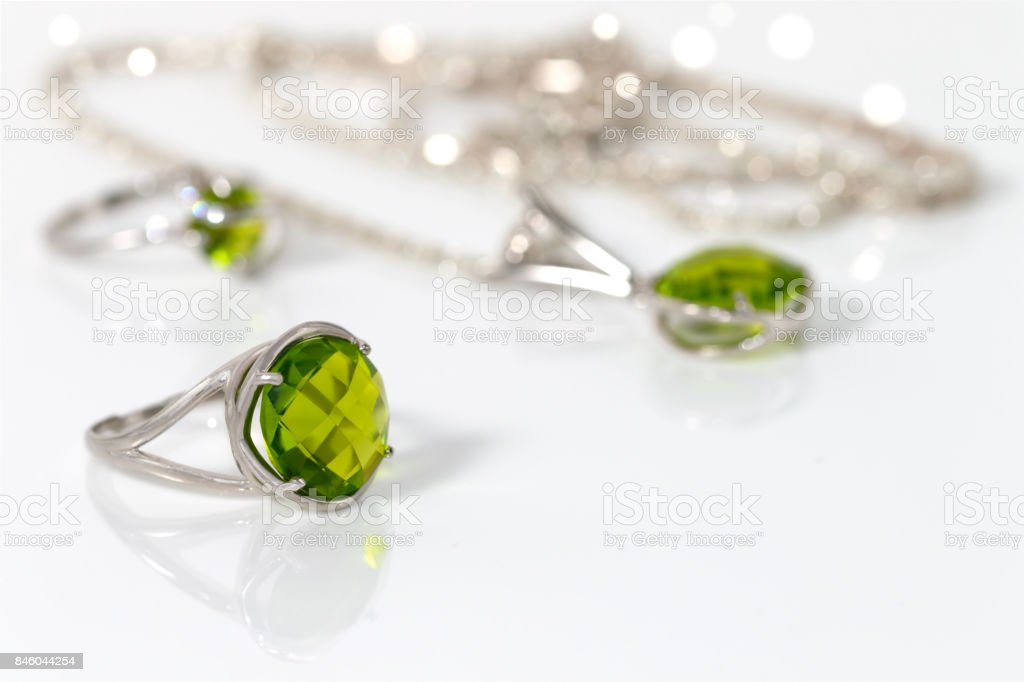 Close-up silver ring with green peridot on background pendant and ring on white acrylic desk. stock photo