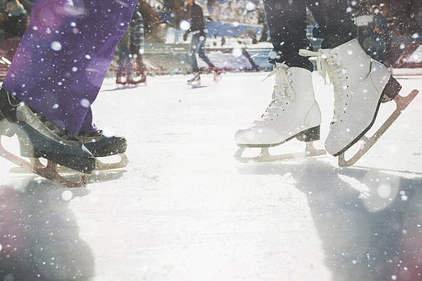 Closeup skating shoes ice skating outdoor at ice rink Closeup skating shoes ice skating outdoor at ice rink. Magical glitter of snowy snowflakes and bokeh. Healthy lifestyle and winter sport concept at sports stadium. ice rink stock pictures, royalty-free photos & images