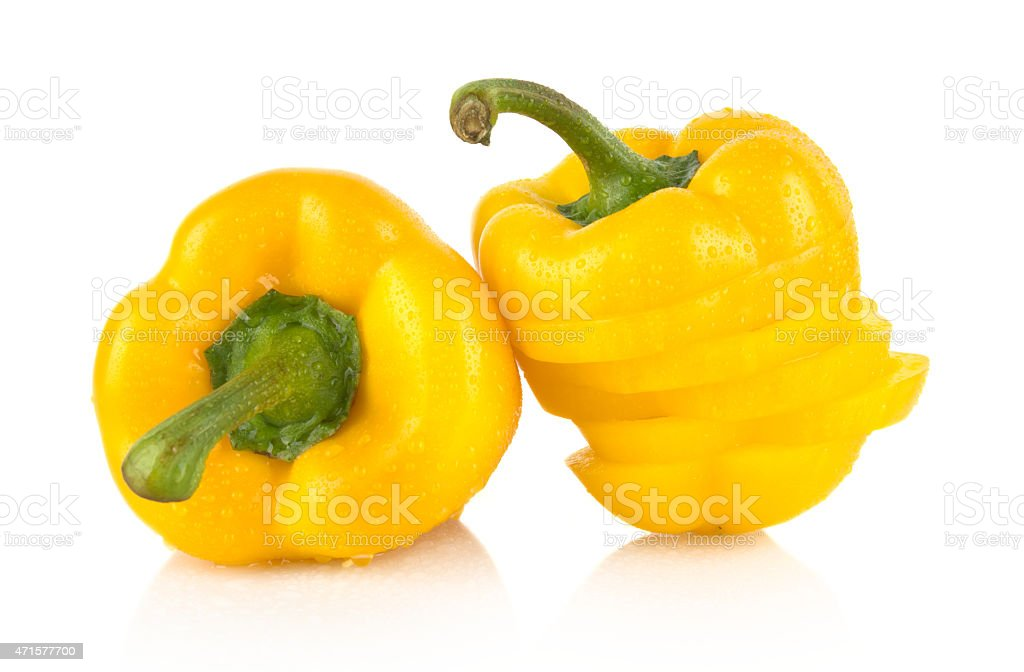 Closeup slices yellow bell peppers on white with drops water stock photo