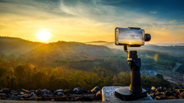 close-up smartphone take a mountians landscape photo and video timelapse on stand mobile stabilizer in sunset - photo messaging stock photos and pictures
