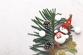 Closeup snowman toy and Christmas decor on white marble. Space for text